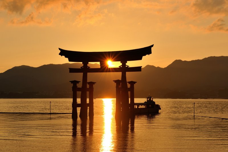 <p>The tide is coming in, and a cruise boat is passing under the big torii gate</p>