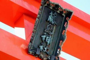赤鳥居に掲げられた重厚な深緑色の藤島神社扁額
