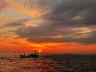 Kapal nelayan yang kecil kembali ke dermaga setelah bekerja seharian