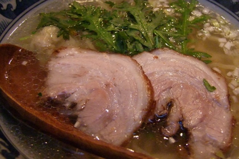 Honmarutei\'s tasty shio-ramen with toppings of sliced pork, chopped spring onion and chrysanthemum leaf.