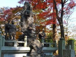 These statues of gods are striking against the fiery colors of the autumn leaves.