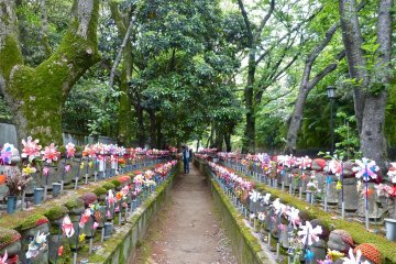 To the right of the cemetery, you will find many small statues wearing red knit caps or aprons. As you might know, they are jizos; people pray to them for their children's happiness.