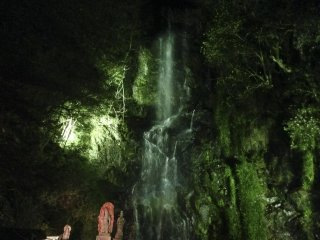 An orange statue of Fudō-Myō-ō (immovable wisdom king) standing steadfast in front of the illuminated green waterfall.