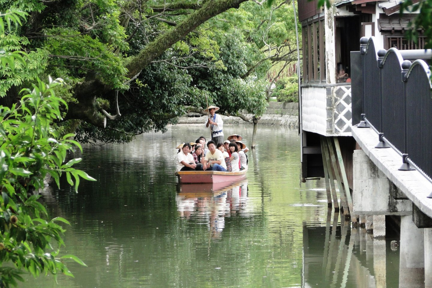 A boat full of visitors makes its way through Yanagawa's canals
