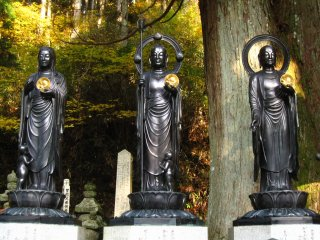 three statues each holding agolden discwith fetus engraved inside