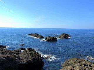 Đá đen nhô ra từ biển xanh