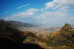 Perbukitan dengan dedaunan musim gugur serta pemandangan kota dari ketinggian