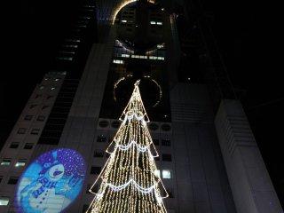 """地上では""""ドイツクリスマスマーケット""""が開催され巨大なツリーがビルを見上げるように立つ"""