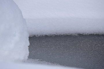 눈으로 둘러싸인 얼어붙은 연못
