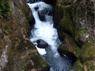 Dòng nước chảy qua một khe núi hẹp từ thác nước trên cao xuống dưới thác nước phía dưới