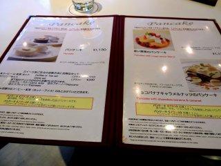 O menú tem uma variedade de comida - panquecas, sanduíches, bolos, etc.
