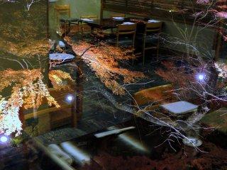 Jardim japonês iluminado visto do meu lugar. O interior do restaurante está refletido na janela.