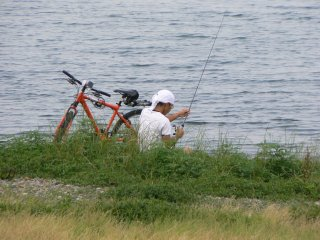 People fish from the shore as well