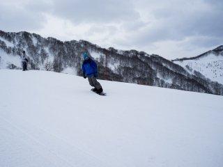 Snowboarder thử nghiệm động thái của mình trên độ dốc của người mới bắt đầu