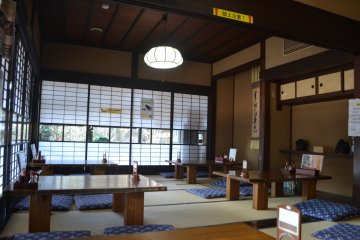 Гостиная главного дома, оформленная в традиционном японском стиле.  Здесь можно пообедать, любуясь двором усадьбы сквозь застекленные юкими сёдзи -  раздвижные перегородки, отделяющие внутренние помещения от пространства двора.