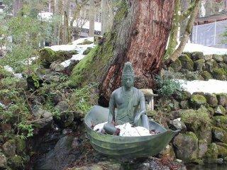 通用門脇の池。岩の上には舟に乗る青銅製の如来像