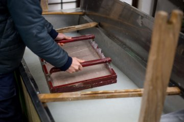 <p>Making the shape of the washi paper from the fiber</p>
