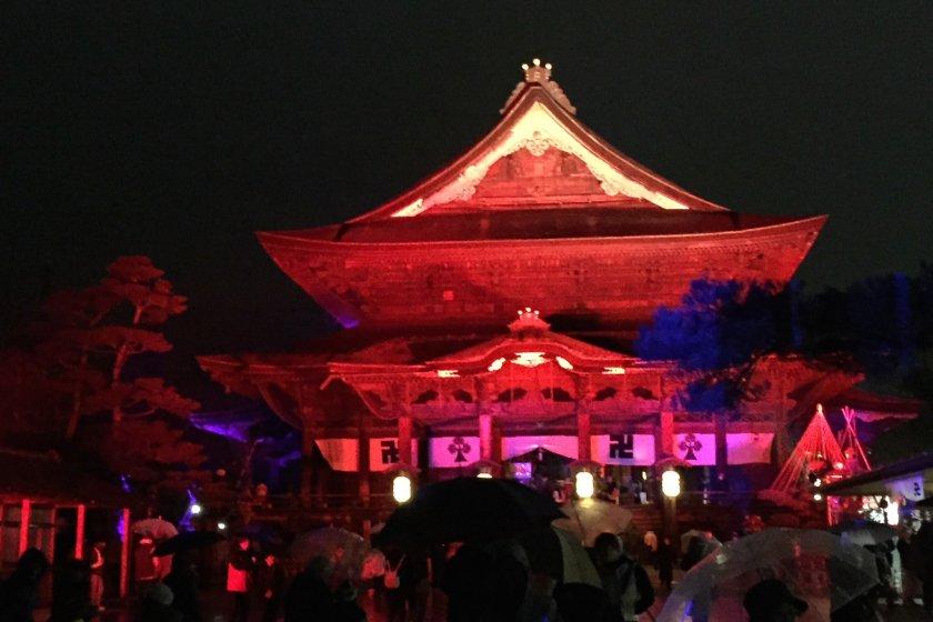 The main hall of Zenkoji, lit up in firey red