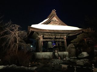 The snow-topped bell pagoda, lit up in yellow