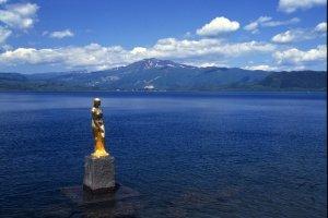 Estátua de Tatsuko no lago Tazawa-ko. Diz-se que Tatsuko terá rezado por juventude e beleza eternas, transformando-se numa deusa do lago.
