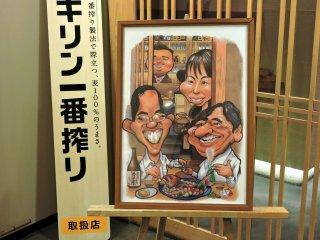 店先に飾られた面白いイラスト: 歓談しながら酒肴を楽しむ客の様子が描かれている