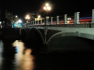 แสงจากโคมไฟบนสะพานข้ามแม่น้ำอะสะโนะสะท้อนภาพลงบนผืนน้ำ