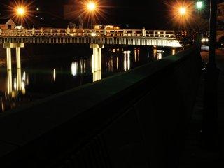แสงไฟจากบนสะพานสะท้อนแสงลงบนผิวน้ำ