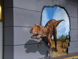 Trick art painting of Fukui-raptor on a wall of JR Fukui Station terminal building