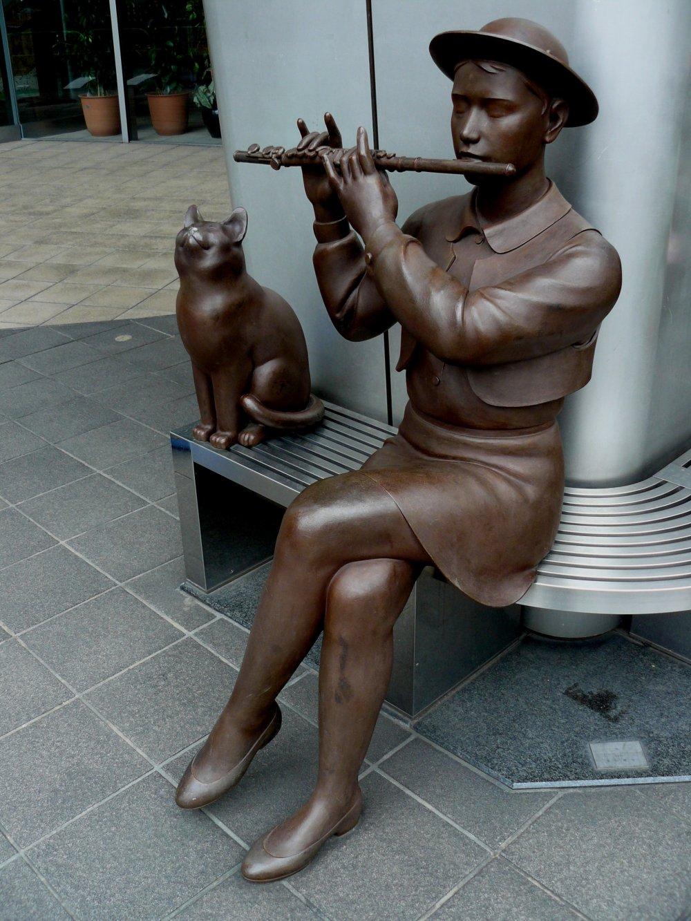 Бронзовая девушка играет на флейте, сидя на лавочке
