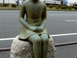 Бронзовая девочка сидит на камне возле дороги