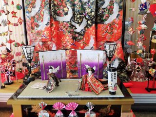 Kimono yang cantik sebagai latar belakang menambah kesan yang istimewa pada sepasang boneka Hina tradisional ini.