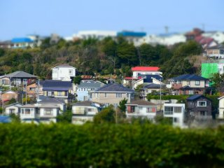 Tilt-shift photo of houses on the hill in the distance from Kamakura Prince Hotel