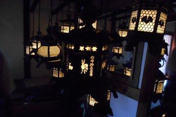 <p>Illuminated lanterns inside the&nbsp;Fujinami-no-ya Hall</p>