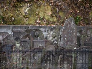 厳めしい顔つきの地蔵と墓石