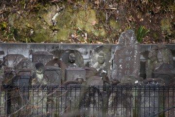 검은 석조 조각상들과 무덤 돌들의 빛나는 얼굴들