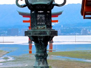 A shrine lantern and torii gate at low tide