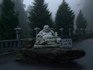 This statue of Hotei, one of the Seven Gods of Fortune, welcomes you at the entrance of the approach