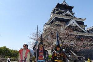 ครอบครัวน่ารักกำลังถ่ายภาพกับปราสาทคุมะโมะโตะ