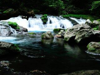 A profundidade da água e a incidência da luz solar transformam o verde do riacho de montanha