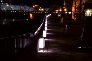 Lit-up paper lanterns on the stone-paved pathway along Asuwa River at night
