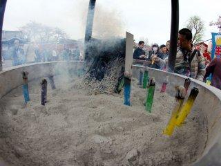 Trước ngôi đền là một khu vực mà bạn có thể mua nhang thắp khoảng ¥100 và đốt lên rồi cắm vào trong cát trong lúc bạn cầu nguyện.