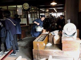 아카후쿠의 가게의 추억의 인테리어 속 일하는 파란 의상을 입은 직원들