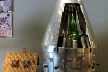 <p>A house made of corks stands next to something that looks a bit like a rocket&#39;s landing pod. &nbsp;</p>
