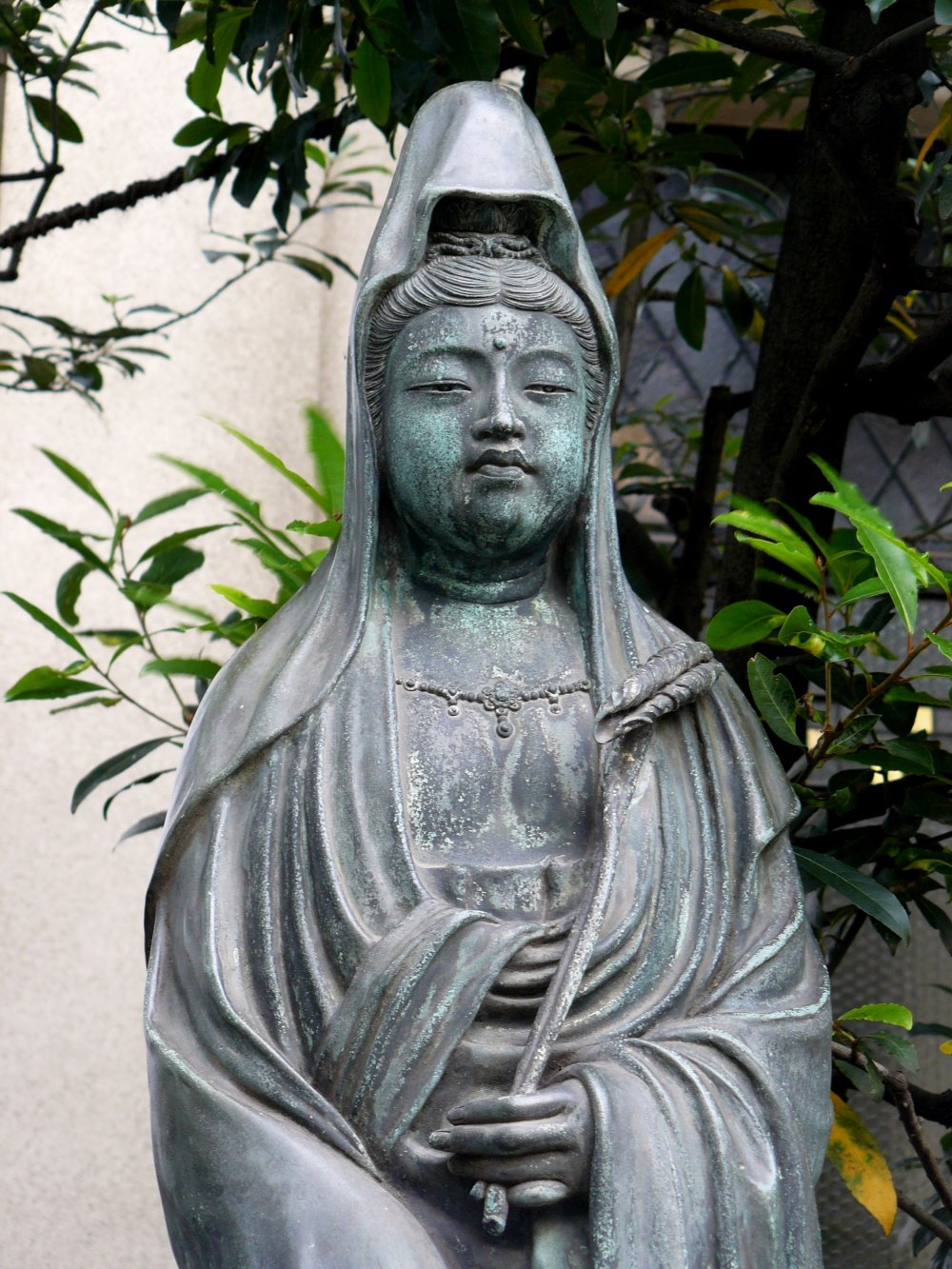 Крупный план боддхисатвы Каннон, держащей лист лотоса
