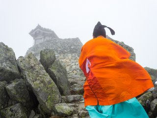 A Shinto priest ascends the final steps to the summit