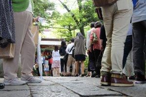 Plusieurs centaines de personnes se rendent au sanctuaire Atago Jinja lors du Sennichi Mari, et l'on fait même la queue pour avoir accès à l'autel