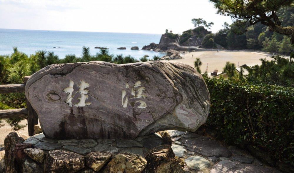 "Karakter kanji ""Katsurahama"" terpahat di batu dekat pantai"