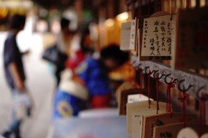 Menulis harapan pada sebuah media kayu dan kemudian digantungkan menjadi salah satu daya tarik bagi turis