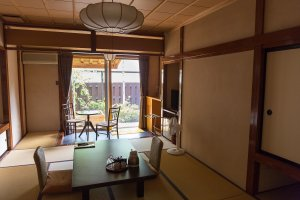 A traditional Japanese style room, featuring tatami mats and a private onsen and garden