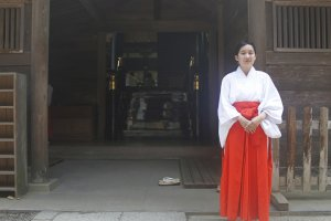 A women stands next to the main shrine.